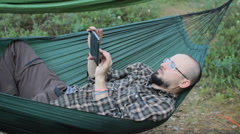 A man in a hammock touch tablet. Man in the woods with a beard and glasses Stock Footage