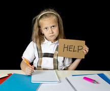 sad and tired cute junior schoolgirl with blond hair sitting in stress working - stock photo
