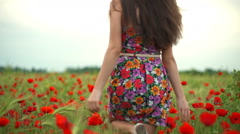 Back view young female walking through the poppy field slow motion Stock Footage