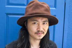 Portrait of mid adult man with hat, blue door in background Stock Photos