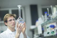 Male scientist holding up flask in lab Stock Photos