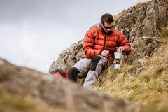 Young male hiker igniting camping stove, The Lake District, Cumbria, UK - stock photo