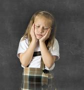 Young sweet junior schoolgirl with blonde hair crying sad and shy Stock Photos