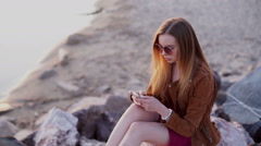 Smartphone woman in red dress sms texting using app on smart phone at beach - stock footage
