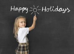 Young sweet junior schoolgirl writing happy holidays on blackboard Stock Photos