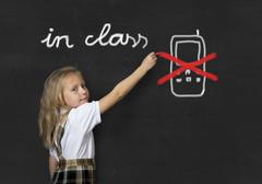 young sweet junior schoolgirl not using mobile phone in class message - stock photo