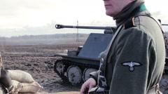 Soldier In WW2 German Uniform Guarding Territory Near Tank - stock footage