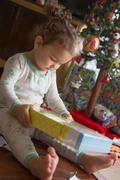 Little girl admiring Christmas gift - stock photo