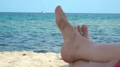 Woman barefoot relaxing on the sand closeup, white boat sailing on blue sea Stock Footage