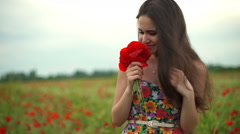young smiling female posing with a bouquet of poppies in a field slow motion - stock footage