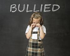 junior schoolgirl crying victim of bullying suffering stress and fear - stock photo