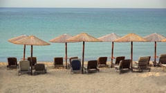 Empty exotic beach with straw umbrellas and blue waters Stock Footage