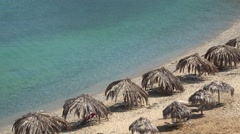 Exotic beach straw umbrellas covered with dry palm leaves and turquoise sea Stock Footage