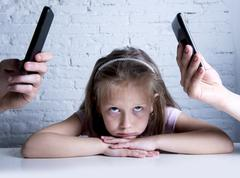Addict mobile phone parents neglecting and ignoring little sad daughter Stock Photos