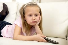 Sweet cute and beautiful 6 or 7 years old girl sad and bored with mobile phone Stock Photos