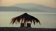 Lounge chairs and palm tree umbrella on the beach at sunset Stock Footage