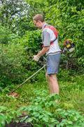 man mows a lawn mower in the garden - stock photo