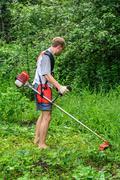 Man mows a lawn mower in the garden Stock Photos