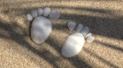 Two soles shaped arrangement of small white pebbles on the fine sand - stock footage