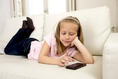 happy blond little girl on home sofa using internet app on mobile phone - stock photo