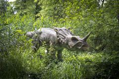 A dinosaur statue in a recreation park, greenery in background Stock Photos
