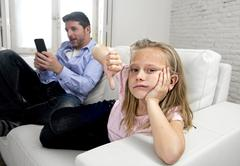 Young internet addict father using mobile phone ignoring his little sad daughter Stock Photos