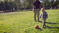 Boy kicking ball in park - stock footage