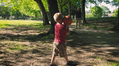 Grandson and grandfather playing with ball in park Stock Footage