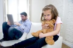 Young internet addict father using digital tablet  ignoring little sad daughter Stock Photos
