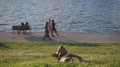 A young girl lying on the grass and people walking along the river bank at sunse Stock Footage
