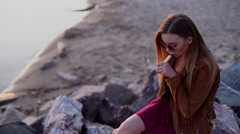 Young beautiful woman smoking ( vaping ) e-cigarette on a sunset beach - stock footage