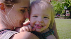 Mother and daughter laughing in park Stock Footage