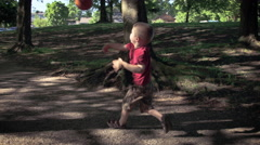 Grandson and grandfather playing with ball in park - stock footage