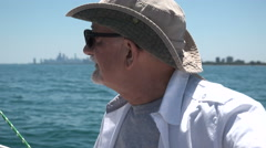 Senior aged man sailing his boat Stock Footage