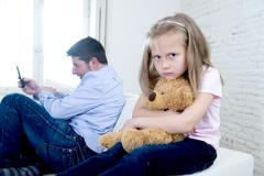 Young internet addict father using mobile phone ignoring little sad daughter Stock Photos