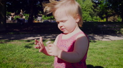 Baby girl playing with dandelion flower in park Stock Footage