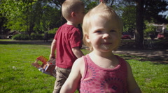 Cute baby girl walking in park Stock Footage