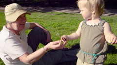 Granddaughter offering dandelion flower to grandmother in park - stock footage