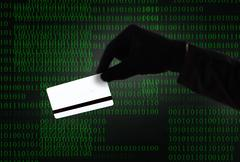 Hacker hand in black glove holding credit card in binary code computer screen Stock Photos