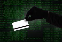 Hacker hand in black glove holding credit card in binary code computer screen Kuvituskuvat