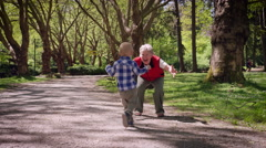 Grandmother playing with her grandson in park Stock Footage
