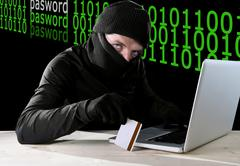Man in black holding credit card using computer laptop for criminal activity Kuvituskuvat