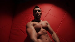 Brutal muscular man in the red room dancing Stock Footage