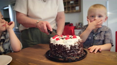 Woman cutting a birthday cake on the table - stock footage