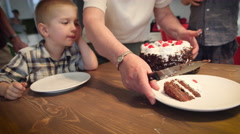 Senior woman serving cake to children on the table Stock Footage