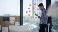 4K Businessman checking messages on phone next to window with sticky notes Stock Footage