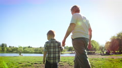Grandmother walking with grandson in park Stock Footage