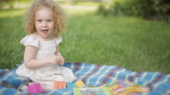 Curly girl in the Park on a blanket playing. Stock Footage