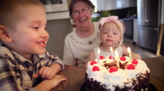 Boy blowing candles on his birthday cake - stock footage