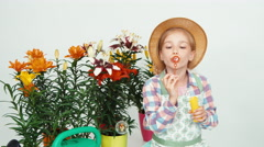 Flower-girl child in hat blowing soap bubbles at camera and smiling with teeth Stock Footage